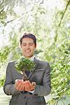 Businessman holding plant outdoors Stock Photo - Premium Royalty-Free, Artist: Rick Gomez, Code: 635-05651480