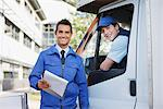 Worker with clipboard standing with truck and driver Stock Photo - Premium Royalty-Freenull, Code: 635-05651508