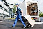 Deliveryman puling boxes on hand truck Stock Photo - Premium Royalty-Free, Artist: Blend Images, Code: 635-05651518