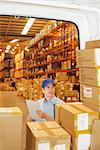 Deliveryman checking boxes in back of van Stock Photo - Premium Royalty-Free, Artist: Blend Images, Code: 635-05651523