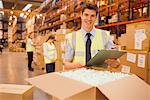 Worker with laptop checking box in warehouse Stock Photo - Premium Royalty-Free, Artist: Ikon Images, Code: 635-05651525