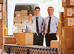 Business people standing with boxes in shipping area Stock Photo - Premium Royalty-Free, Artist: Blend Images, Code: 635-05651552