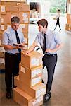 Businessmen standing together with stack of boxes
