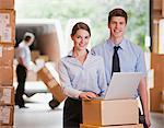 Business people working with laptop in warehouse Stock Photo - Premium Royalty-Free, Artist: Blend Images, Code: 635-05651581