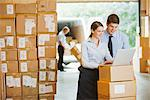 Business people using laptop in warehouse Stock Photo - Premium Royalty-Freenull, Code: 635-05651595