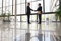 Businessmen shaking hands in office lobby Stock Photo - Premium Royalty-Freenull, Code: 635-05651616