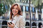 Smiling businesswoman text messaging on cell phone Stock Photo - Premium Royalty-Free, Artist: Dana Hursey, Code: 635-05651645