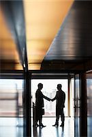 Businessmen shaking hands in corridor Stock Photo - Premium Royalty-Freenull, Code: 635-05651689