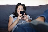 Woman reclining on sofa with cell phone Stock Photo - Premium Royalty-Freenull, Code: 635-05651713