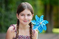 preteen  smile  one  alone - Smiling girl holding pinwheel outdoors Stock Photo - Premium Royalty-Freenull, Code: 635-05651739