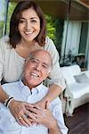 Smiling couple hugging on patio Stock Photo - Premium Royalty-Freenull, Code: 635-05651759