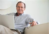 Man sitting on sofa with laptop Stock Photo - Premium Royalty-Freenull, Code: 635-05651847