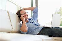 Man reclining on sofa talking on cell phone Stock Photo - Premium Royalty-Freenull, Code: 635-05651861