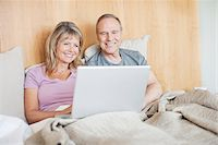 Couple sitting in bed using laptop together Stock Photo - Premium Royalty-Freenull, Code: 635-05651862