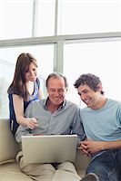 Friends using laptop together Stock Photo - Premium Royalty-Freenull, Code: 635-05651865