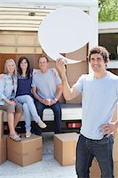 Friends unloading moving van, one man holding comment bubble Stock Photo - Premium Royalty-Freenull, Code: 635-05652139