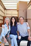 Friends sitting on back of moving van Stock Photo - Premium Royalty-Free, Artist: Blend Images, Code: 635-05652173