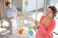Expectant mother looking at crib mobile Stock Photo - Premium Royalty-Freenull, Code: 635-05652250