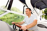 Man steering boat on river Stock Photo - Premium Royalty-Freenull, Code: 635-05652292