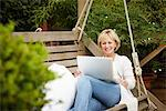 Woman sitting on swing using laptop Stock Photo - Premium Royalty-Freenull, Code: 635-05652314
