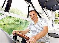 Man driving boat on river Stock Photo - Premium Royalty-Freenull, Code: 635-05652331
