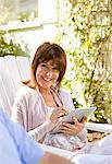 Woman using digital tablet in backyard Stock Photo - Premium Royalty-Freenull, Code: 635-05652341