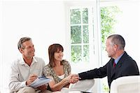 Couple shaking hands with financial advisor Stock Photo - Premium Royalty-Freenull, Code: 635-05652365