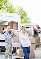 Couple carrying carpet from moving van Stock Photo - Premium Royalty-Freenull, Code: 635-05652432