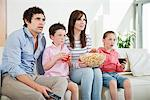 Family intently watching movie on sofa Stock Photo - Premium Royalty-Freenull, Code: 635-05655728