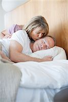 Senior woman kissing man asleep in bed Stock Photo - Premium Royalty-Freenull, Code: 635-05655739