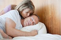 Senior woman kissing man on cheek in bed Stock Photo - Premium Royalty-Freenull, Code: 635-05655790