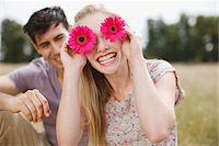 funny pose - Portrait of playful woman holding flowers over eyes in rural field Stock Photo - Premium Royalty-Freenull, Code: 635-05655833