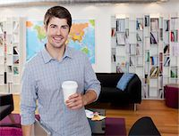 Portrait of smiling businessman with coffee cup in office Stock Photo - Premium Royalty-Freenull, Code: 635-05655984