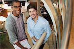 Portrait of smiling architects with blueprint tubes on stairs in office Stock Photo - Premium Royalty-Freenull, Code: 635-05656027