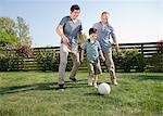 Multi-generation family playing soccer in backyard Stock Photo - Premium Royalty-Free, Artist: Blend Images, Code: 635-05656128
