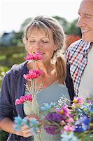 Senior couple smelling flowers in garden Stock Photo - Premium Royalty-Freenull, Code: 635-05656172