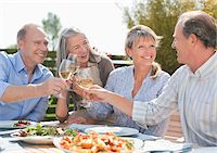 Senior couples toasting wine glasses at patio table Stock Photo - Premium Royalty-Freenull, Code: 635-05656176