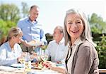 Portrait of smiling woman drinking wine at patio table with friends Stock Photo - Premium Royalty-Freenull, Code: 635-05656189