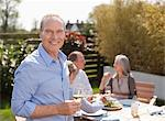 Portrait of smiling man drinking wine in garden with friends Stock Photo - Premium Royalty-Freenull, Code: 635-05656199