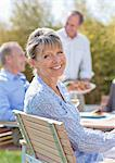 Portrait of smiling senior woman enjoying lunch at table in sunny garden Stock Photo - Premium Royalty-Freenull, Code: 635-05656204