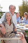 Portrait of smiling senior couple enjoying lunch with friends at table in sunny garden Stock Photo - Premium Royalty-Freenull, Code: 635-05656228