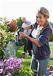 Senior woman watering flowers in garden with watering can Stock Photo - Premium Royalty-Freenull, Code: 635-05656232