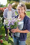 Portrait of smiling woman holding potted flower in garden Stock Photo - Premium Royalty-Freenull, Code: 635-05656246