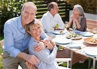 Portrait of smiling senior couple sitting at table in sunny garden Stock Photo - Premium Royalty-Freenull, Code: 635-05656258