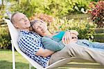 Serene senior couple with eyes closed laying in lounge chair in garden Stock Photo - Premium Royalty-Freenull, Code: 635-05656274