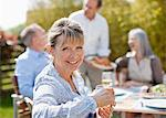 Portrait of smiling senior woman enjoying lunch with friends at sunny table Stock Photo - Premium Royalty-Freenull, Code: 635-05656292