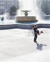 Man lifting woman in front of urban fountain Stock Photo - Premium Royalty-Freenull, Code: 635-05656304