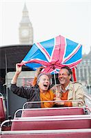 Rain falling on couple with British Flag umbrella on double decker bus Stock Photo - Premium Royalty-Freenull, Code: 635-05656306