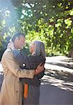 Couple hugging on sunny road under trees Stock Photo - Premium Royalty-Freenull, Code: 635-05656308