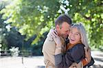 Portrait of smiling couple hugging in sunny park Stock Photo - Premium Royalty-Freenull, Code: 635-05656316